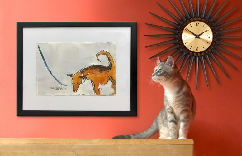 Cat sitting on a shelf next to a piece of art.